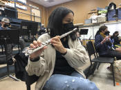 FILE - In this March 2, 2021 file photo, a student plays the flute while wearing a protective face mask during a music class at the Sinaloa Middle School in Novato, Calif. With COVID-19 cases soaring nationwide, school districts across the U.S. are yet again confronting the realities of a polarized country and the lingering pandemic as they navigate mask requirements, vaccine rules and social distancing requirements for the fast-approaching new school year. (AP Photo/Haven Daily)