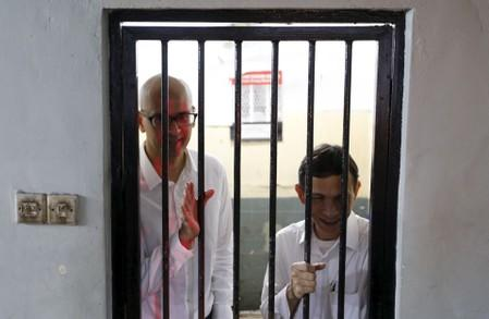 FILE PHOTO: Canadian teacher Neil Bantleman waves beside Indonesian teaching assistant Ferdinand Tjiong to students as they wait inside a holding cell before their trial at a South Jakarta court