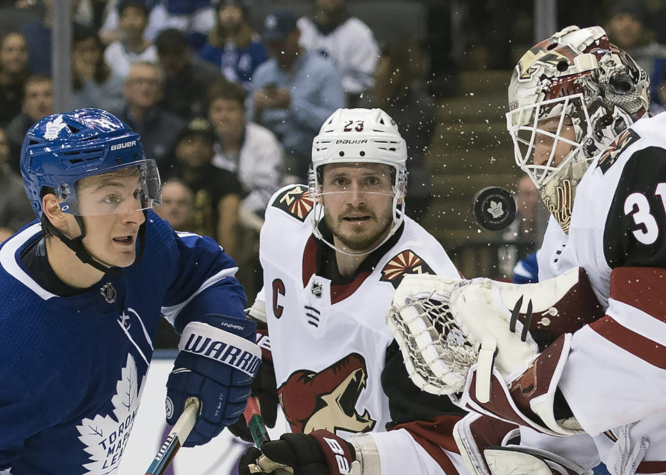 Arizona Coyotes goaltender Adin Hill (31) makes a save as Toronto Maple Leafs left wing Zach Hyman (11) eyes the puck during the second period of an NHL hockey game, Tuesday, Feb. 11, 2020 in Toronto. (Nathan Denette/The Canadian Press via AP)
