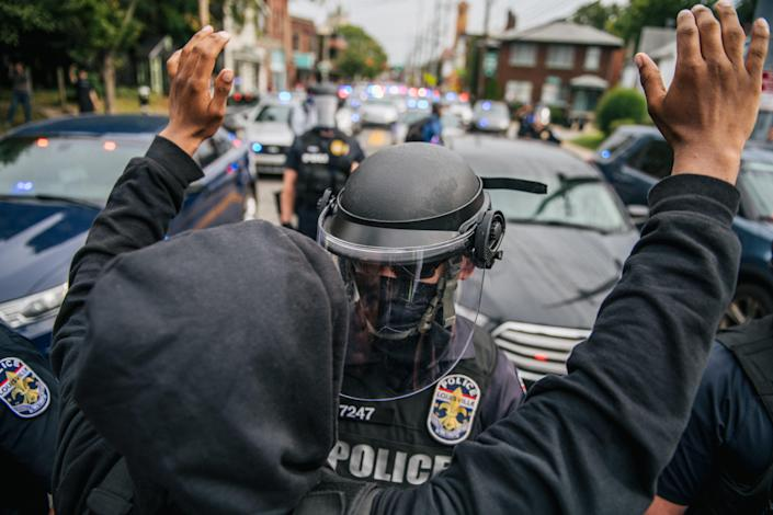 A protester raises his hands in the air during a standoff with law enforcement on September 23, 2020 in Louisville, Kentucky. / Credit: Brandon Bell / Getty Images