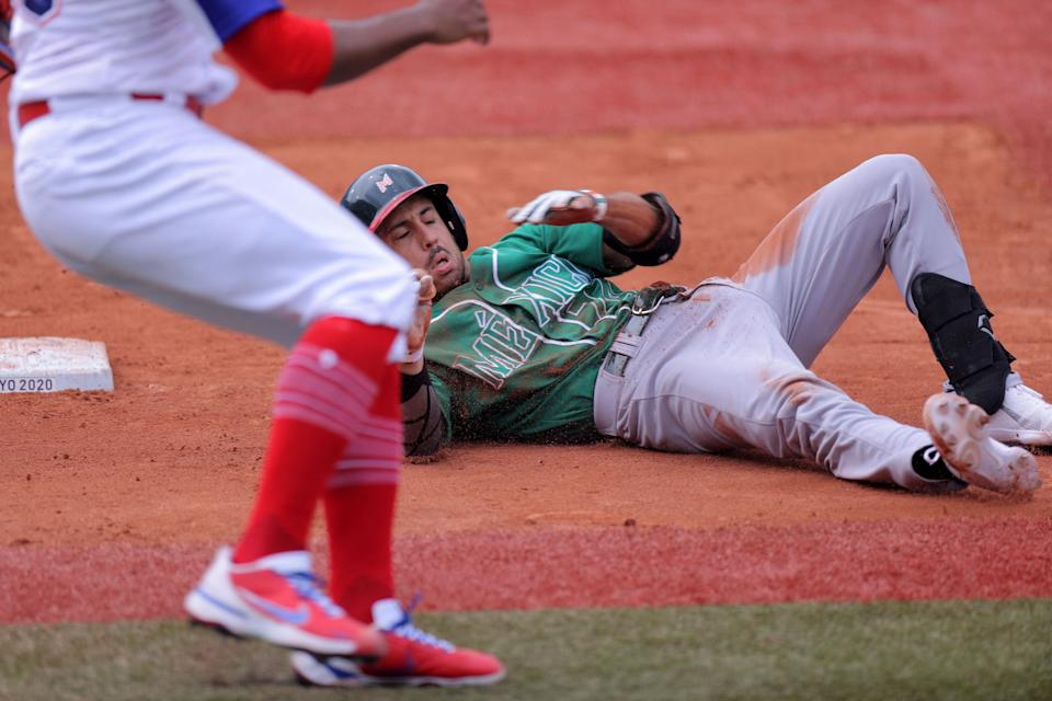 Mexico's Isaac Rodriguez (R) falls after being collided with Dominican Republic's pitcher Ramon Rosso (L) at the first base during the sixth inning of the Tokyo 2020 Olympic Games baseball opening round group A game between Mexico and Dominican Republic at Yokohama Baseball Stadium in Yokohama, Japan, on July 30, 2021. (Photo by KAZUHIRO FUJIHARA / AFP) (Photo by KAZUHIRO FUJIHARA/AFP via Getty Images)
