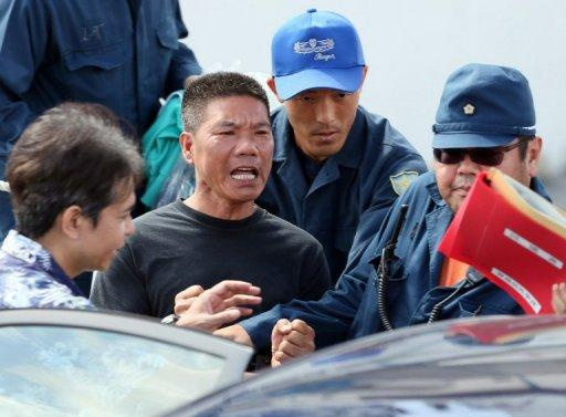A pro-China activist (C), one of 14 that landed on the disputed island known as Senkaku in Japan and Diaoyu in China, is arrested by police at Naha port on Japan's sourthern island of Okinawa, on August 16. Japan is now considering what to do with the arrested activists as Beijing has angrily demanded their immediate release