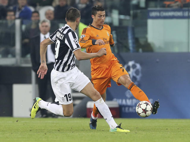 Real's Cristiano Ronaldo, right, is challenged by Juventus' Leonardo Bonucci during a Champions League, Group B, soccer match between Juventus and Real Madrid at the Juventus stadium in Turin, Italy, Tuesday, Nov. 5, 2013. (AP Photo/Antonio Calanni)