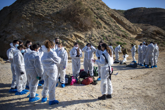 Israeli soldiers wearing protective suits listen to a briefing ahead of cleanup operations to remove tar from a beach after an oil spill in the Mediterranean Sea At Sharon Beach Nature Reserve, near Gaash, Israel, Monday, Feb. 22, 2021. (AP Photo/Ariel Schalit)