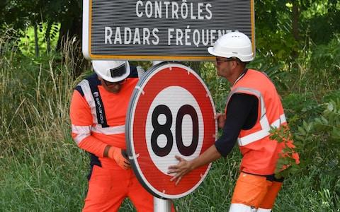 Workers set an 80 kph speed limit sign up on the national road RN2 in Grenade in southwestern France, June 2018. - Credit: PASCAL PAVANI/AFP