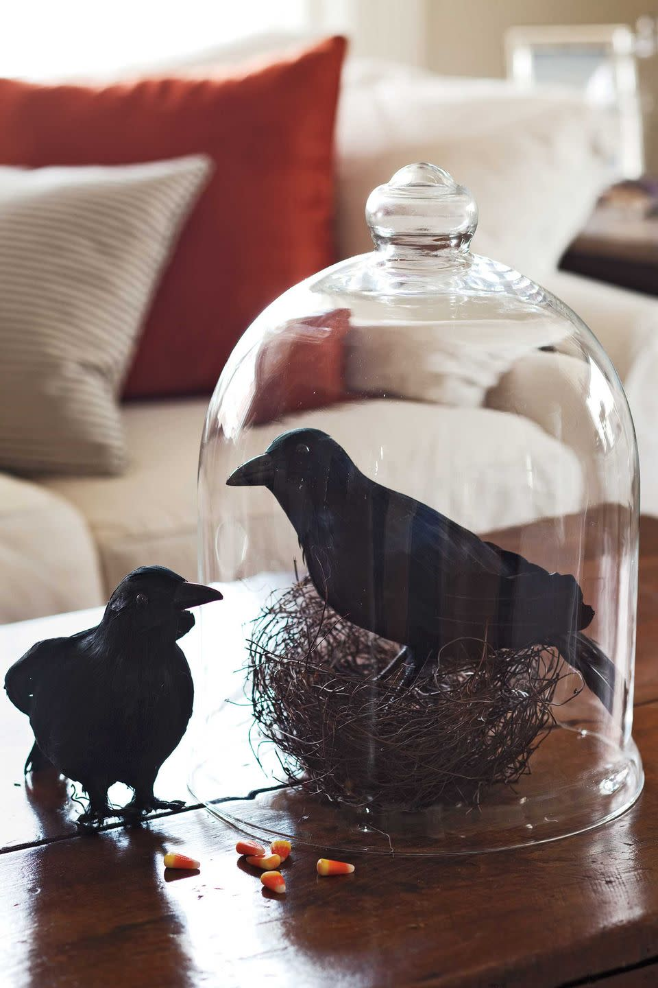 """<p>Serve up a helping of raven under glass with craft store crows and a real or faux nest under a glass hurricane. Nevermore, nevermore! </p><p><strong>What You'll Need</strong>: <a href=""""https://www.amazon.com/Touch-Black-Feathered-Ravens-Halloween/dp/B07KGD8RTQ/ref=sr_1_5?dchild=1&keywords=fake+raven&qid=1594918771&sr=8-5&tag=syn-yahoo-20&ascsubtag=%5Bartid%7C10070.g.1279%5Bsrc%7Cyahoo-us"""" rel=""""nofollow noopener"""" target=""""_blank"""" data-ylk=""""slk:Fake birds"""" class=""""link rapid-noclick-resp"""">Fake birds</a> ($17, Amazon); <a href=""""https://www.amazon.com/Industrial-Medium-Desert-Dessert-Display/dp/B01L5ZQD6S/ref=sr_1_5?dchild=1&keywords=glass+dessert+topper&qid=1594997079&sr=8-5&tag=syn-yahoo-20&ascsubtag=%5Bartid%7C10070.g.1279%5Bsrc%7Cyahoo-us"""" rel=""""nofollow noopener"""" target=""""_blank"""" data-ylk=""""slk:glass topper"""" class=""""link rapid-noclick-resp"""">glass topper</a> ($28, Amazon)</p>"""