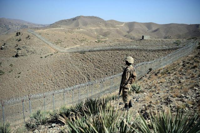 A Pakistani soldier keeps vigil next to a newly fenced border fencing along Afghan border at Kitton Orchard Post in Pakistan's North Waziristan tribal agency on October 18, 2017. The Pakistan military vowed on October 18 a new border fence and hundreds of forts would help curb militancy, as it showcased efforts aimed at sealing the rugged border with Afghanistan long crossed at will by insurgents. / AFP PHOTO / AAMIR QURESHI (Photo credit should read AAMIR QURESHI/AFP/Getty Images)