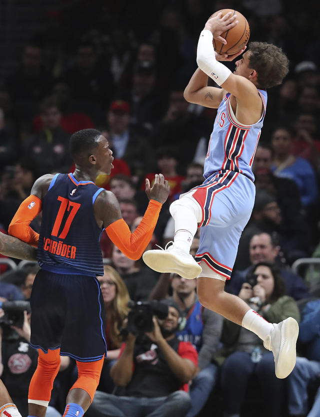 Atlanta Hawks guard Trae Young shoots over Oklahoma City Thunder guard Dennis Schroder during the second half of an NBA basketball game on Tuesday, Jan. 15, 2019, at State Farm Arena in Atlanta. (Curtis Compton/Atlanta Journal-Constitution via AP)