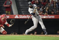 Seattle Mariners' Domingo Santana, right, hits a solo home run as Los Angeles Angels catcher Jonathan Lucroy watches during the seventh inning of a baseball game Friday, June 7, 2019, in Anaheim, Calif. (AP Photo/Mark J. Terrill)
