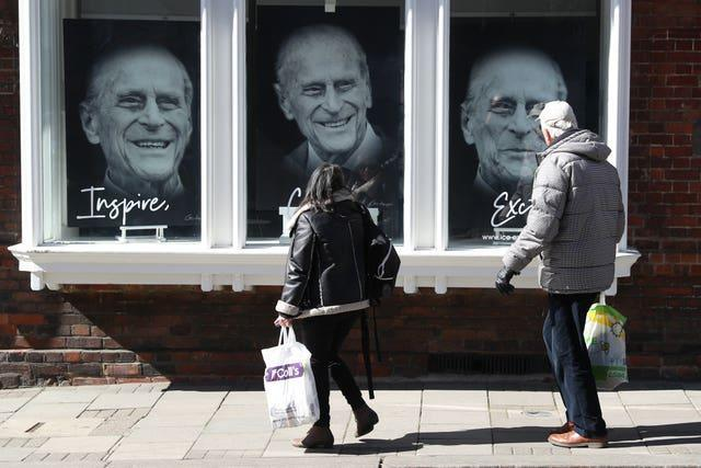 Members of the public walk past a gallery in Windsor High Street, containing pictures of the duke (Andrew Matthews/PA)