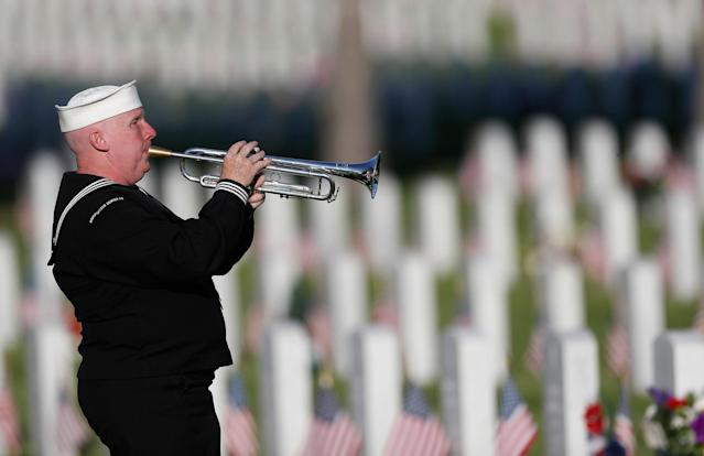 <p>Playing a tribute to veterans at gravesites to mark the Memorial Day holiday, retired U.S. Navy Yeoman Mark Stallins of Denver performs in Fort Logan National Cemetery on May 28, 2017, in southwest Denver. (Photo: David Zalubowski/AP) </p>
