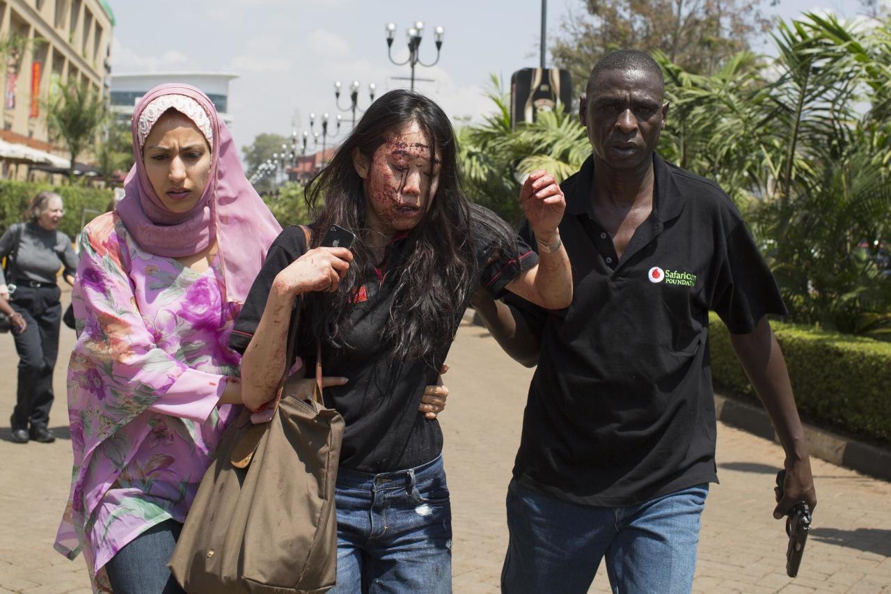 An injured woman (C) is helped out of the Westgate Shopping Centre where gunmen went on a shooting spree, in Nairobi September 21, 2013. The gunmen stormed the shopping mall in Nairobi on Saturday killing at least 20 people in what Kenya's government said could be a terrorist attack, and sending scores fleeing into shops, a cinema and onto the streets in search of safety. Sporadic gun shots could be heard hours after the assault started as soldiers surrounded the mall and police and soldiers combed the building, hunting down the attackers shop by shop. REUTERS/Siegfried Modola (KENYA - Tags: CIVIL UNREST TPX IMAGES OF THE DAY)