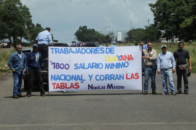 """FILE PHOTO: Workers of CVG hold a banner that reads """"Workers of Guayana. 1800 minimun wage and adjust the pay scales"""" during a protest in Puerto Ordaz"""