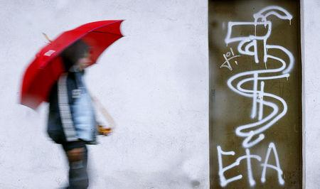 FILE PHOTO: A boy walks past graffiti of armed separatist group ETA in the Basque town of Guernica, Spain March 21, 2004. REUTERS/Vincent West/File Photo
