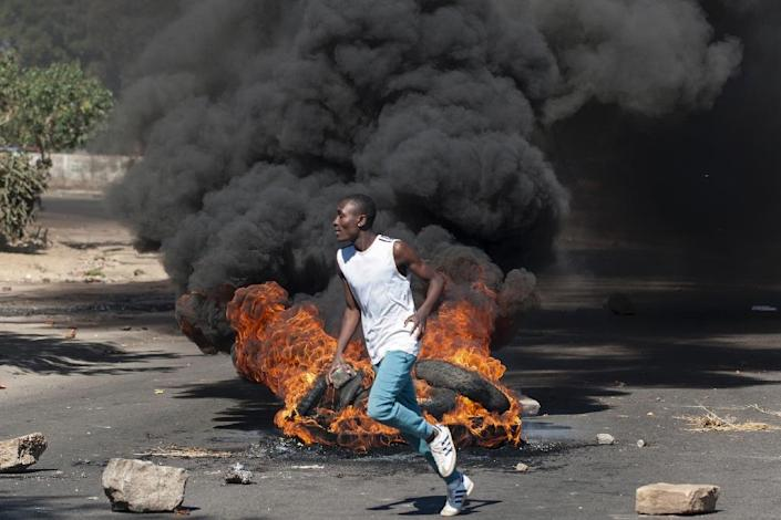A protester throws rocks next to burning tyres during a demonstration in Bulawayo, southern Zimbabwe on July 6, 2016 (AFP Photo/)