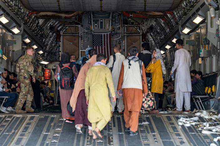 A U.S. Air Force loadmaster, assigned to the 816th Expeditionary Airlift Squadron, assists evacuees aboard a C-17 Globemaster III aircraft in support of Operation Allies Refuge at Hamid Karzai International Airport, Kabul, Afghanistan, on Aug. 20.