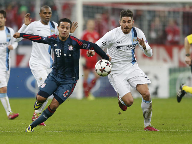 Bayern's Thiago Alcantara, left, and Manchester City's Javi Garcia challenge for the ball during the Champions League group D soccer match between FC Bayern Munich and Manchester City, in Munich, southern Germany, Tuesday, Dec. 10, 2013. (AP Photo/Matthias Schrader)