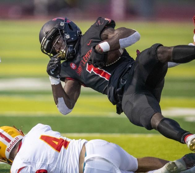 San Clemente, CA - April 16: San Clemente running back James Bohls leaps over a tackling Mission Viejo linebacker Brenndan Warady in the second quarter at San Clemente High School on Friday, April 16, 2021 in San Clemente, CA. (Allen J. Schaben / Los Angeles Times)