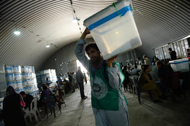 An election commission worker carries a ballot box during an audit of the presidential run-off vote in the country's general election at a counting centre in Kabul on August 25, 2014 (AFP Photo/Wakil Kohsar)