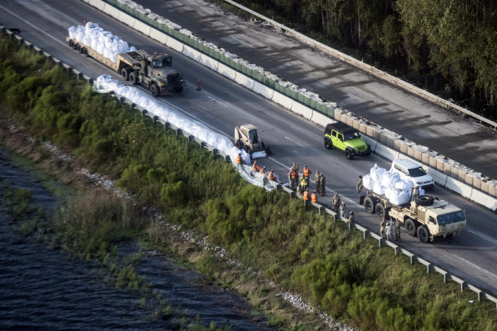 As traffic heads to the beach, emergency crews build a temporary dam protecting U.S. 501 from floodwaters after Florence struck the Carolinas, Monday, Sept. 17, 2018, in Conway, S.C. (AP Photo/Sean Rayford)