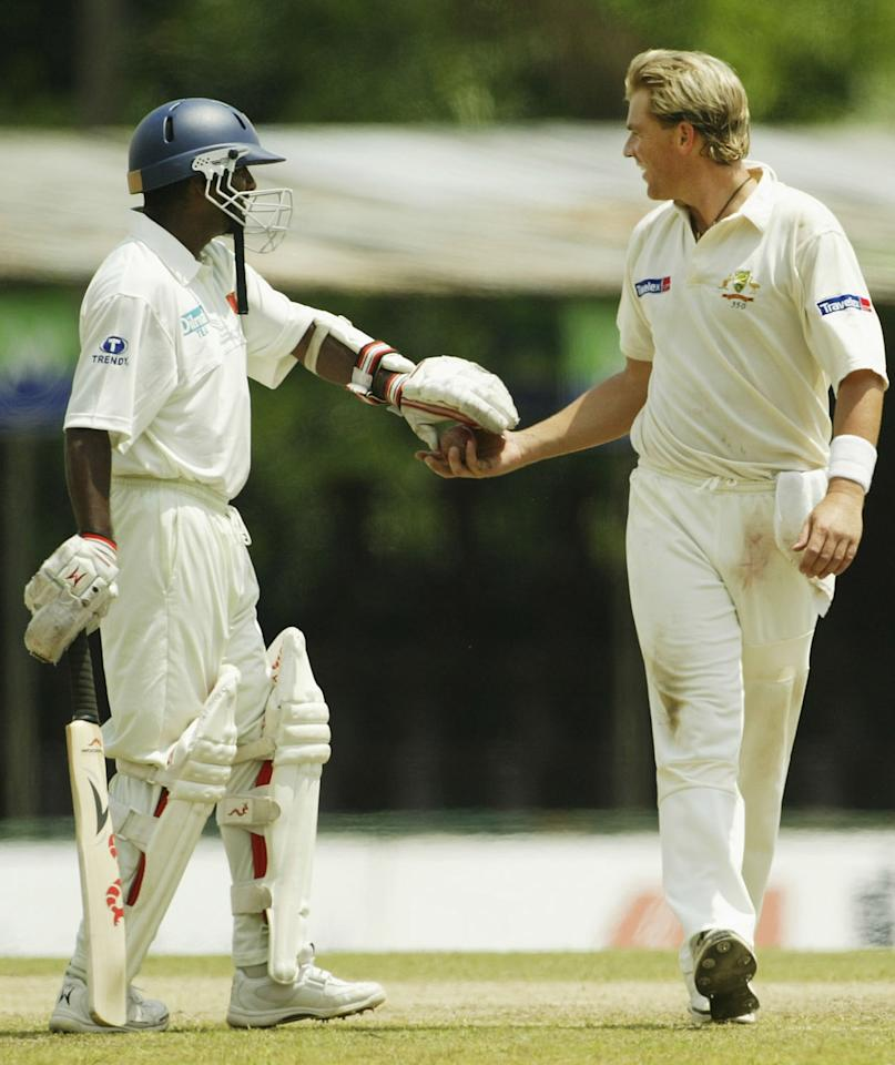 KANDY, SRI LANKA - MARCH 17:  Muttiah Muraltharan of Sri Lanka hands the ball to Shane Warne of Australia during day two of the Second Test between Australia and Sri Lanka played at Asgiriya Stadium on March 17, 2004 in Kandy, Sri Lanka. (Photo by Hamish Blair/Getty Images)