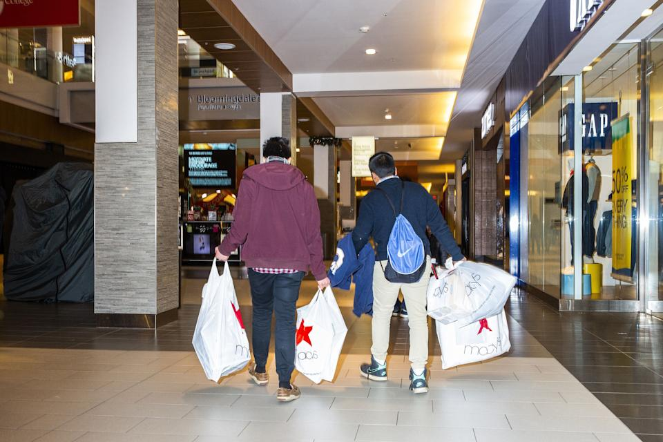 Shoppers hold Macy's Inc. shopping bags at the Simon Property Group Roosevelt Field mall in Garden City, New York, U.S., on Thursday, Nov. 22, 2018. Deloitte expects sales from November to January to rise as much as 5.6 percent, to more than $1.1 trillion, marking the best holiday period in recent memory. Photographer: David Williams/Bloomberg via Getty Images