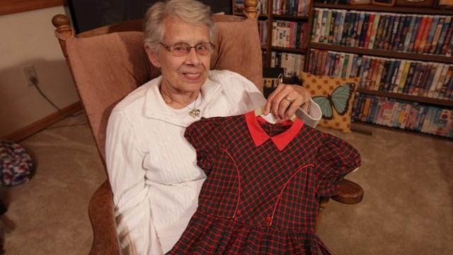 Jan Parker holds the dress worn for elementary school photos by 17 of her daughters and granddaughters. (Photo: Chad Nelson, KARE 11)