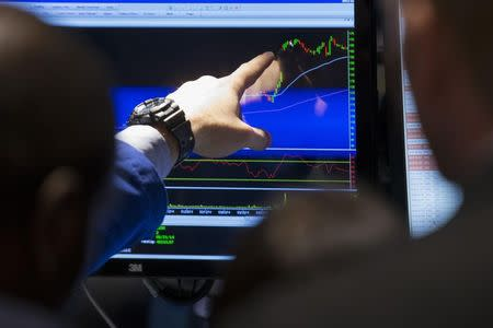 A specialist trader points at the price movement of a stock while working on the floor of the New York Stock Exchange