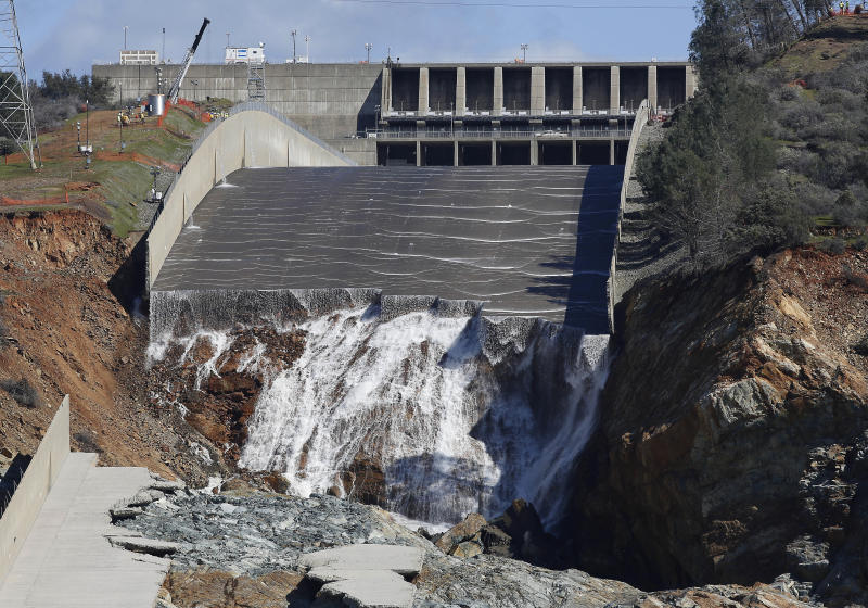 FILE - In this Feb. 28, 2017 file photo, water goes down Oroville Dam's crippled spillway in Oroville, Calif. Over six days, operators of the tallest dam in the United States, struggled to figure out their next move after raging floodwaters from California's wettest winter in decades gouged a hole the size of a football field in the dam's main water-release spillway. (AP Photo/Rich Pedroncelli, File)