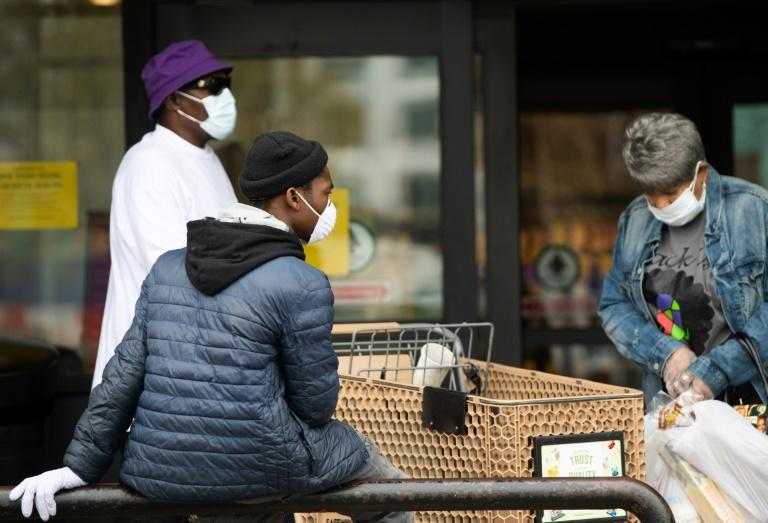 People wearing masks to try and prevent the spread of COVID-19 leave a supermarket in Washington, DC, April 7, 2020