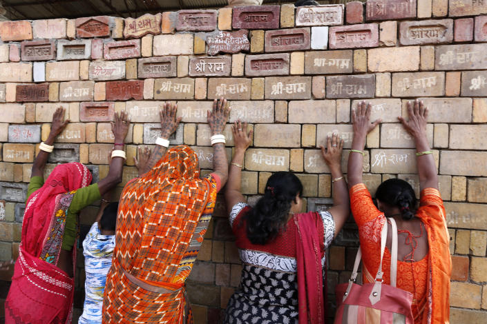 """FILE - In this Nov. 11, 2019, file photo, Hindu women devotees pray to the bricks reading """"Shree Ram"""" (Lord Ram), which are expected to be used in constructing Ram temple, in Ayodhya, India. As Hindus prepare to celebrate the groundbreaking of a long-awaited temple at a disputed ground in northern India, Muslims say they have no firm plans yet to build a new mosque at an alternative site they were granted to replace the one torn down by Hindu hard-liners decades ago. (AP Photo/Rajesh Kumar Singh, File)"""