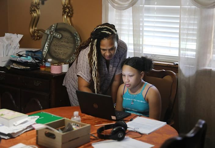 LaTonya Alexander tries to help daughter, fifth grader Abigail, set up for virtual learning at home on her first day of school Tuesday, Aug. 3, 2020, in Nashville. Students are starting the school year virtually. Abigail attends Head Middle Magnet School.