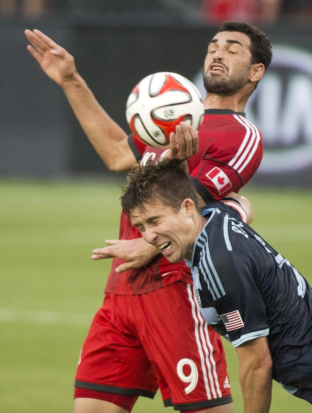 Toronto FC defender Doneil Henry, rear, competes for the ball against Sporting Kansas City forward C.J. Sapong during the first half of an MLS soccer game Saturday, July 26, 2014, in Toronto. (AP Photo/The Canadian Press, Nathan Denette)