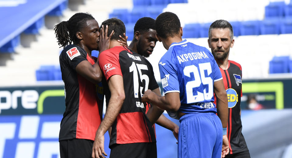 Hertha's Dedryck Boyata either kissed or whispered to teammate Marko Grujic after a goal was scored on Saturday, violating the Bundesliga's social distancing guidelines for celebrations. (Photo by Thomas Kienzle/Pool via Getty Images)