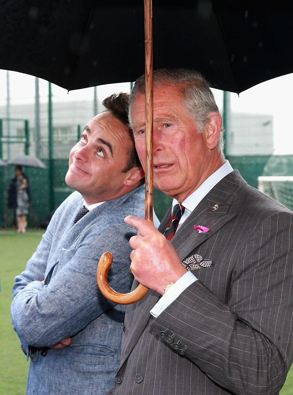 <p>TV presenter Anthony McPartlin enjoys the shelter provided by Prince Charles's umbrella.<br></p>