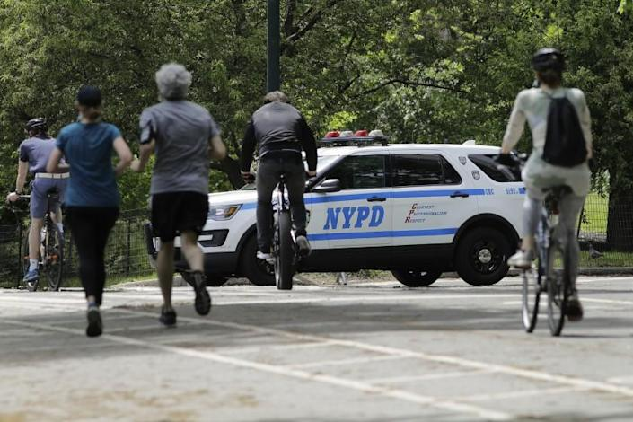 "Runners and cyclists pass a New York City police vehicle in Central Park on Saturday. <span class=""copyright"">(Frank Franklin II / Associated Press)</span>"