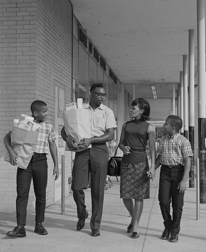 <p>As seen here, a family of four leaves the store carrying paper bags full of groceries. It wouldn't be for about another decade, until the 1970s, that the plastic bag quickly rose to prominence. </p>