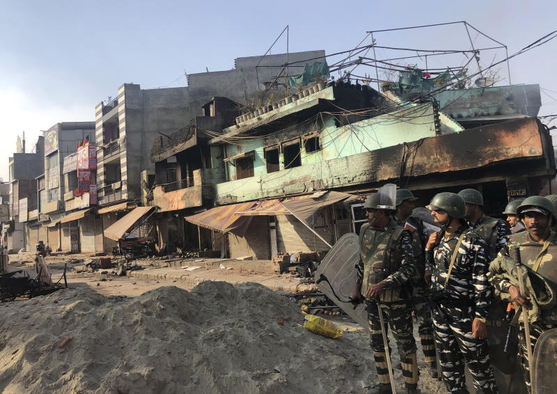 Indian security officers guard a street in a locality experiencing violence between two groups in Bhajanpura are of New Delhi, India, Tuesday, Feb. 25, 2020. At least seven people, including a police officer, were killed and dozens injured in the clashes, police said Tuesday. (AP Photo/Sheikh Saaliq)