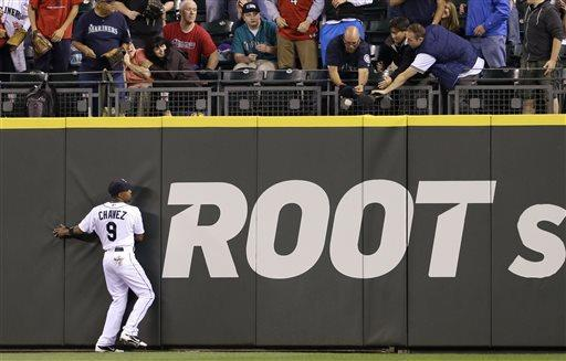Seattle Mariners center fielder Endy Chavez watches as fans reach for the home run ball of Pittsburgh Pirates' Russell Martin in the second inning of a baseball game Tuesday, June 25, 2013, in Seattle. (AP Photo/Elaine Thompson)
