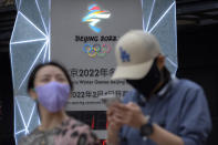 """People wearing face masks to protect against COVID-19 walk past a display showing a countdown clock to the Beijing 2022 Winter Olympics in Beijing, Wednesday, Aug. 18, 2021. China's """"zero tolerance"""" strategy of trying to isolate every case and stop transmission of the coronavirus has kept kept the country where the virus first was detected in late 2019 largely free of the disease. (AP Photo/Mark Schiefelbein)"""