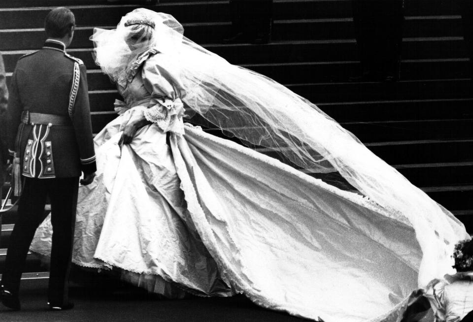 Lady Diana Spencer, soon to become the Princess of Wales, showing her wedding gown for the first time, turns as her bridesmaids set her train on arrival at Saint Paul's Cathedral for her wedding to Prince Charles in London, July 29, 1981. REUTERS/Mal Langsdon (BRITAIN  - Tags: ENTERTAINMENT ROYALS) BEST QUALITY AVAILBLE