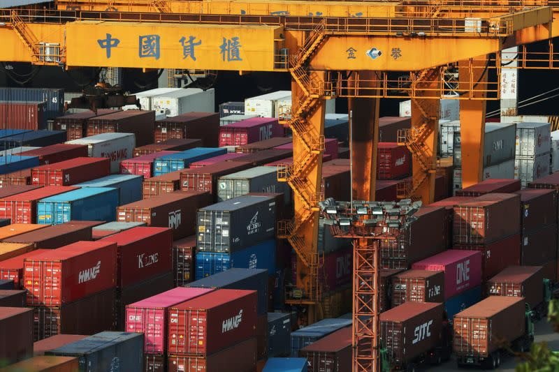 FILE PHOTO: Trucks wait to be loaded on with containers at a port in Keelung