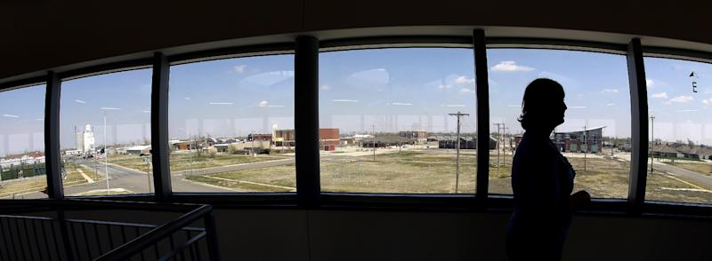 In this photo taken April, 18, 2014, museum director Stacy Barnes looks out over scattered rebuilt homes and business from a viewing deck at the rebuilt Big Well Museum in Greensburg, Kan. Seven years after an EF-5 tornado destroyed most of the community of 1,500, many of the town's destroyed civic buildings have been rebuilt but a rebound in population is slow in coming. (AP Photo/Charlie Riedel)