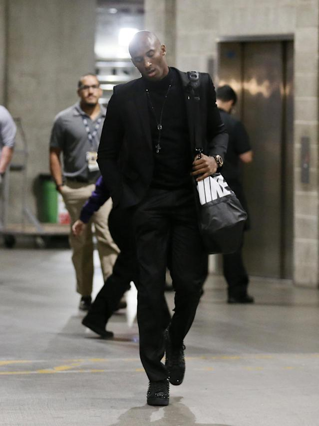 Los Angeles Lakers' Kobe Bryant arrives at Staples Center before the NBA basketball game against the Toronto Raptors in Los Angeles, Sunday, Dec. 8, 2013. Bryant is expected to make his long-awaited return from a torn left Achilles tendon injury from April 12th. (AP Photo/Danny Moloshok)