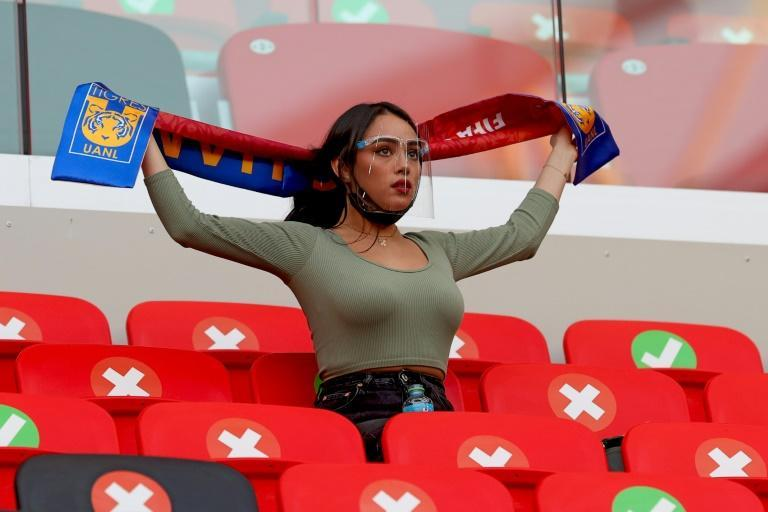 A socially-distanced Tigres fan leaves nothing to chance, wearing a coronavirus face shield during her side's clash against Ulsan