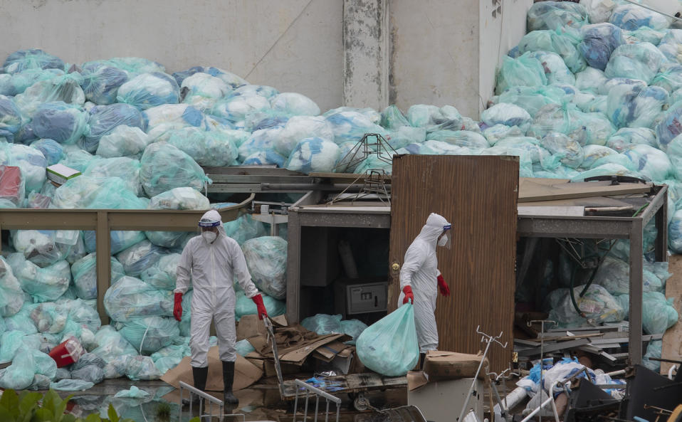 Medical workers using protective equipment dispose of trash bags containing hazardous biological waste into a large pile outside the Hospital del Instituto Mexicano del Seguro Social, which treats patients with COVID-19 in Veracruz, Mexico, Wednesday, Aug. 12, 2020. Improper disposal of medical waste has become an increasing problem in Mexico amid the pandemic. (AP Photo/Felix Marquez)