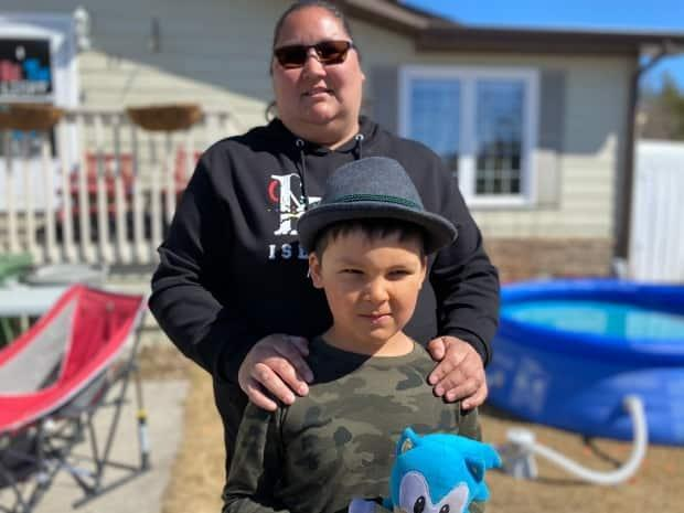 Renee Sanderson stands with her nine-year-old son, Kane, outside their Yellowknife home in spring of 2021. Sanderson was one of many parents who had just over 12 hours to figure out how togo back toremote learning as of Thursday. (John Van Dusen/CBC - image credit)