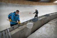 Workers clear the ice at the National Sledding Center in Yanqing on the outskirts of Beijing, Friday, Feb. 5, 2021. Beijing Olympic organizers showed off the downhill skiing venue and the world's longest bobsled and luge track Friday, one year ahead of the scheduled opening of the 2022 Olympic Winter Games. (AP Photo/Mark Schiefelbein)