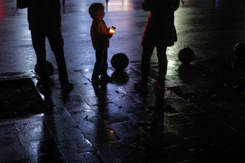 A boy holding a lit candle looks at his mother while they attend an event ment to commemorate the 65 victims of the Colectiv fire