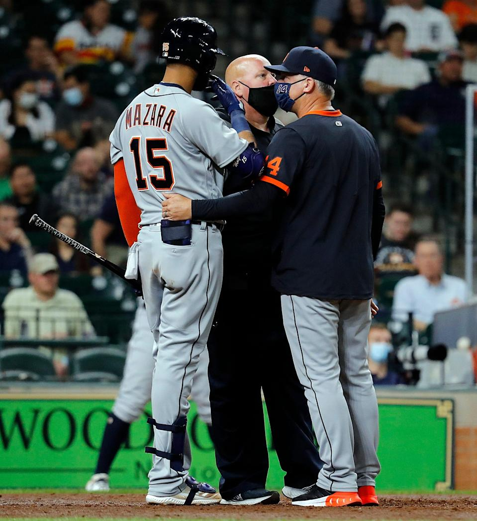 Nomar Mazara #15 of the Detroit Tigers is looked at by the trainer and manager A.J. Hinch #14 after an injury at-bat in the fourth inning against the Houston Astros at Minute Maid Park on April 14, 2021 in Houston, Texas.